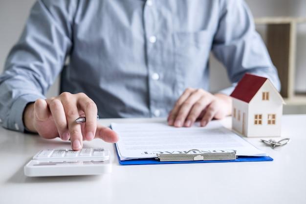 Geschäftsmann, der finanzen und berechnungskosten der immobilieninvestition tuend arbeitet