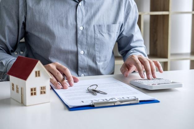 Geschäftsmann, der finanzen und berechnungskosten der investition tuend arbeitet, beim unterzeichnen, um vertrag abzuschließen