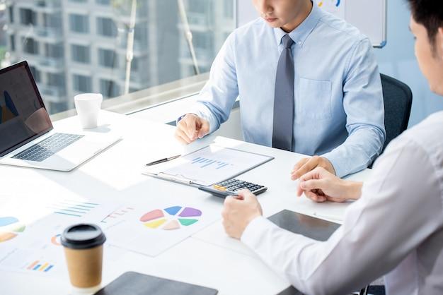 Geschäftsmann, der finanzprognose und statistiken mit kunden im büro bespricht