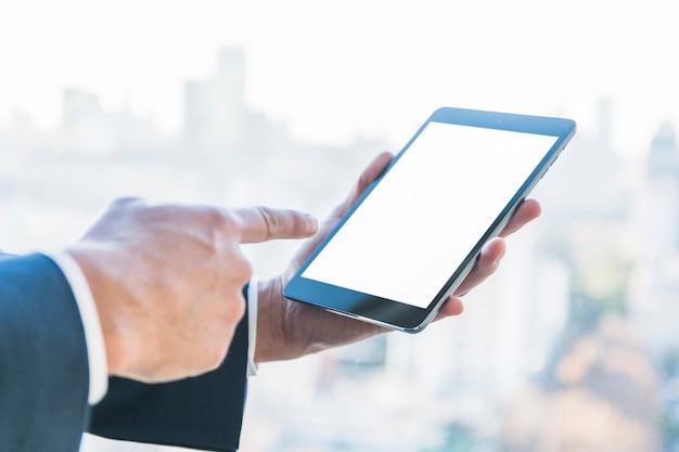 Geschäftsmann, der finger auf digitale tablette mit leerem bildschirm zeigt