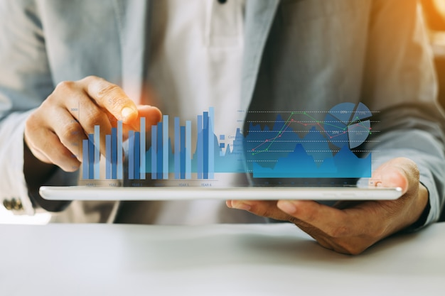 Geschäftsmann, der firmenfinanzberichtbalance mit digitalen grafiken der vergrößerten realität analysiert.