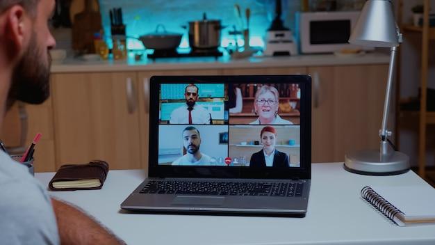 Geschäftsmann, der firmenmeeting mit laptop hat, der spät nachts aus der ferne arbeitet. verwenden sie moderne technologie, um um mitternacht drahtlos in einer videokonferenz zu sprechen und überstunden zu machen