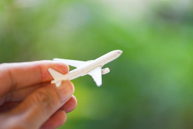 Geschäftsmann, der flugzeugflugzeug des flugzeugs auf naturgrün hält. reisefreiheit reisekonzept