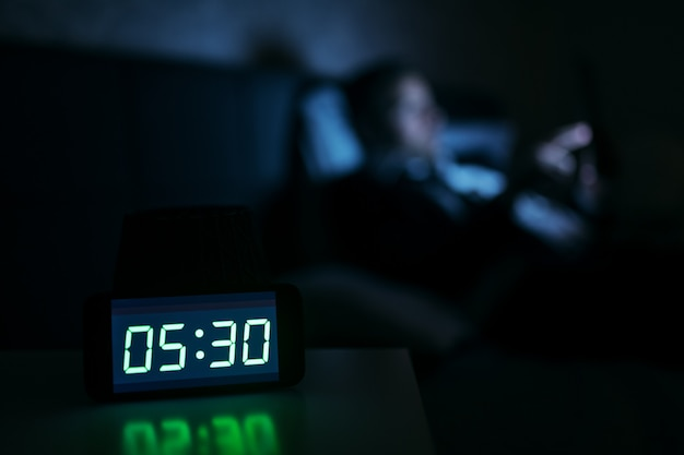 Geschäftsmann, der früh am morgen auf dem bett liegt und tablette benutzt. uhr zeigt 5:30. selektiver fokus auf die uhr.