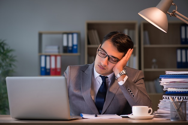 Geschäftsmann, der für lange stunden im büro bleibt