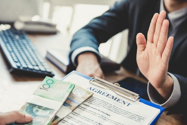 Geschäftsmann, der geld ablehnt, das mit vereinbarung papier kommt