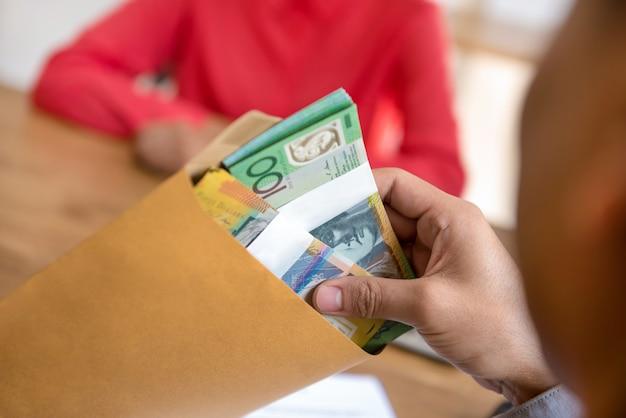 Geschäftsmann, der geld, australische dollar, im umschlag prüft