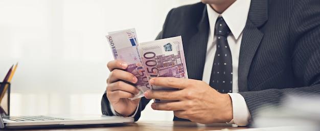 Geschäftsmann, der geld, eurobanknoten, an seinem arbeitsschreibtisch zählt