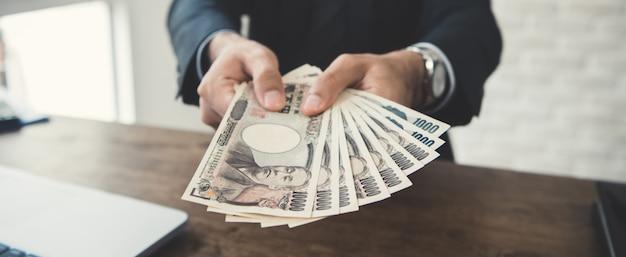 Geschäftsmann, der geld gibt, japanische yen-banknoten
