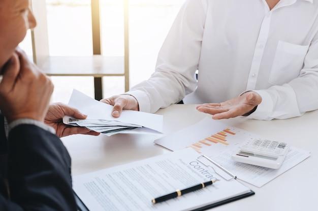 Geschäftsmann, der geld im umschlag bei der herstellung des abkommens zur vereinbarung ein immobilien gibt