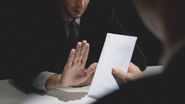 Geschäftsmann, der geld im weißen umschlag zurückweist
