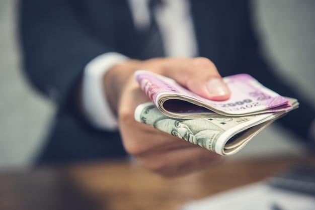 Geschäftsmann, der geld in form von währung der indischen rupien gibt