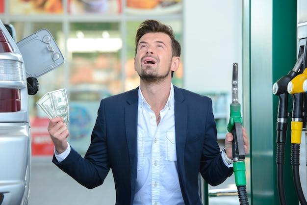 Geschäftsmann, der geld mit benzinbetankung zählt.