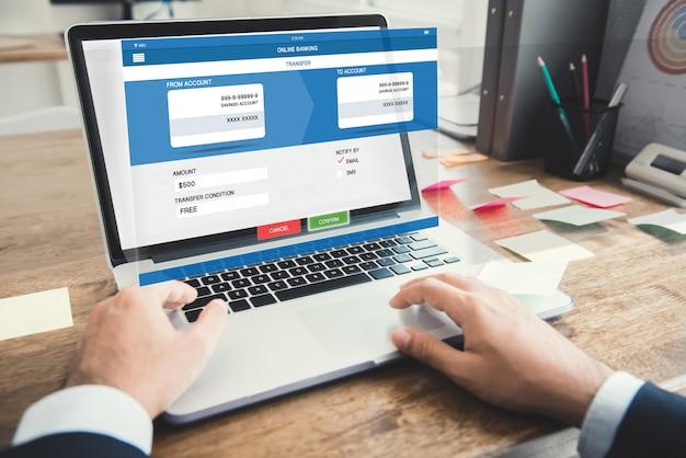 Geschäftsmann, der geld mit internet-on-line-ebankverkehr überträgt