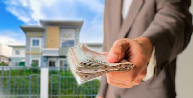 Geschäftsmann, der geld mit unscharfem haus gibt