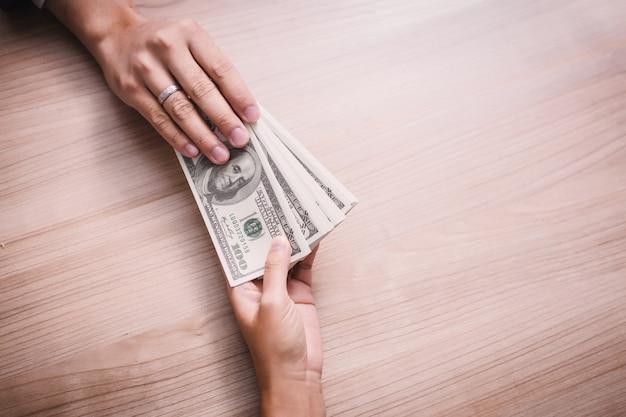 Geschäftsmann, der geld- rechnungen des dollars (usd) der vereinigten staaten zahlt