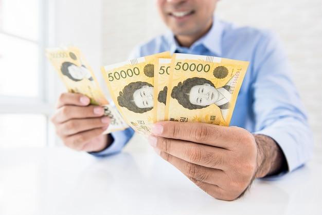 Geschäftsmann, der geld, südkoreanische gewonnene banknoten, am tisch zählt