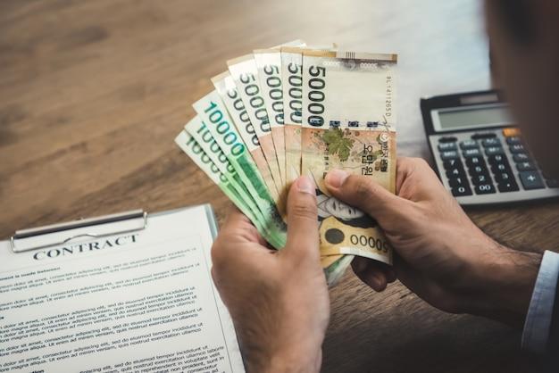 Geschäftsmann, der geld, südkoreanische gewonnene banknoten, mit einem vertrag und einem taschenrechner auf seinem schreibtisch zählt