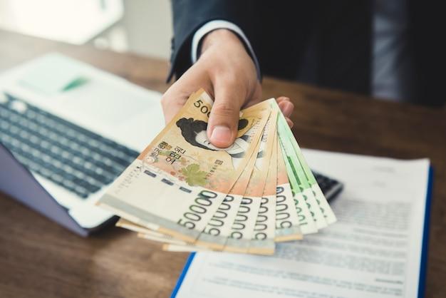 Geschäftsmann, der geld, südkoreanische gewonnene währung, am arbeitsschreibtisch gibt