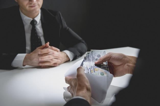 Geschäftsmann, der geld, us-dollar, im umschlag vom partner erhält