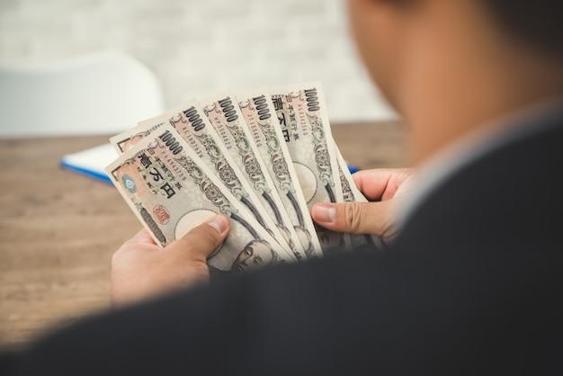 Geschäftsmann, der geld zählt, japanische yen-rechnungen - rückansicht