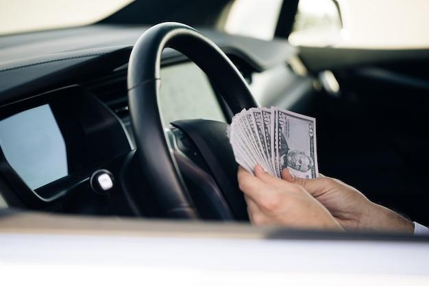 Geschäftsmann, der geld zählt usd rechnungen zahltag im auto
