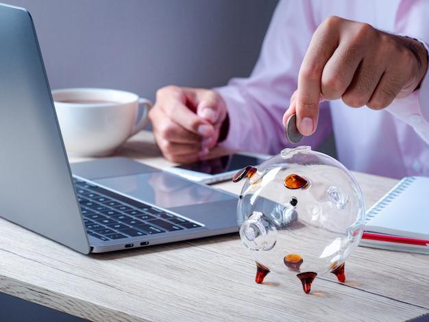 Geschäftsmann, der geldmünzen hält, die im sparschwein auf holztisch im büro setzen. sparen von geld für zukunftspläne und pensionsfonds, spar- und investitionsgelder für unternehmen oder finanzen
