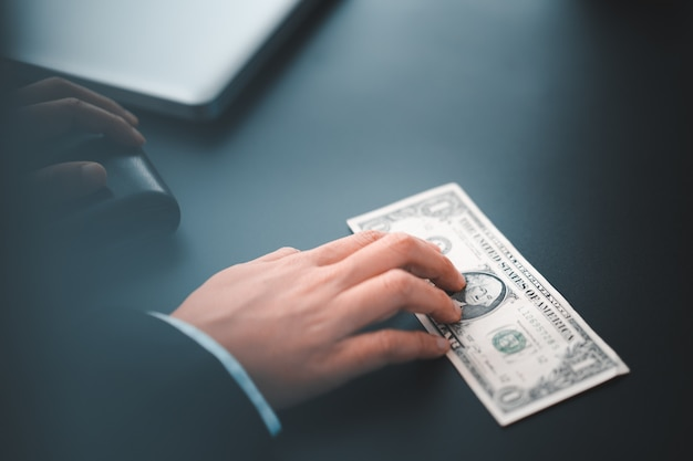 Geschäftsmann, der geldschein auf schwarzem schreibtisch im büro hält