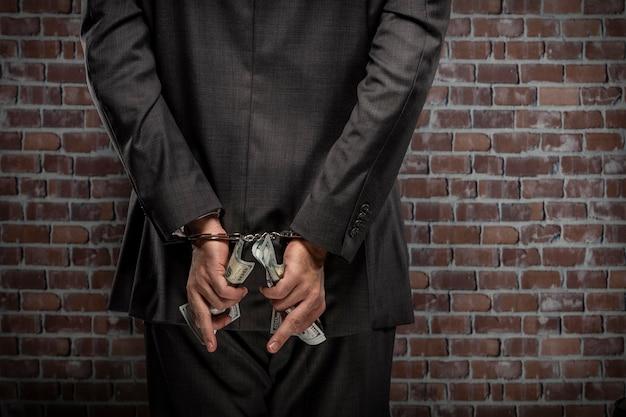 Geschäftsmann, der geldscheine mit einer handschelle in einem gefängnis hält. konzept der korruption, korrupte politiker, illegale unternehmen. backsteinhintergrund.