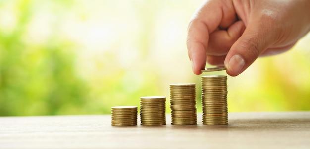 Geschäftsmann, der geldstapel auf tabellenkonzept-einsparungsfinanzierung und -buchhaltung setzt