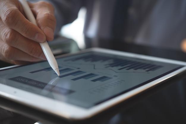 Geschäftsmann, der geschäftsbericht auf digitalem tablet-computer analysiert
