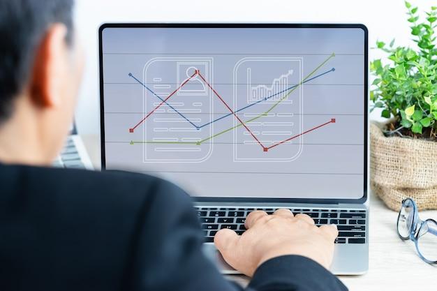 Geschäftsmann, der geschäftsergebnisse im quartal mit digitaler finanzberichtsdiagrammschicht auf laptop-computer analysiert und verkaufs- oder statistikdiagramme im arbeitsplatzbüro zeigt. ideen für jahresberichte
