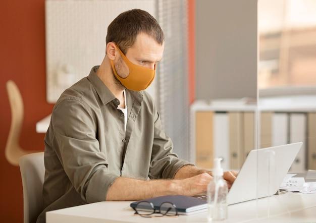Geschäftsmann, der gesichtsmaske im büro trägt