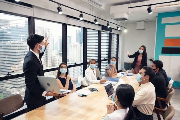 Geschäftsmann, der gesichtsmaske mit präsentation des geschäftsplans auf laptop trägt