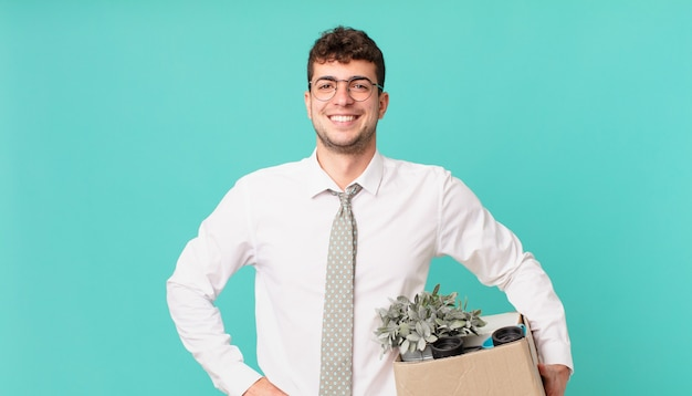 Geschäftsmann, der glücklich mit einer hand auf hüfte und selbstbewusster, positiver, stolzer und freundlicher haltung lächelt. kündigungskonzept