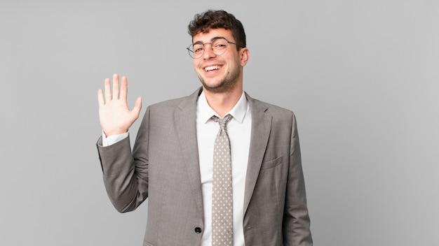 Geschäftsmann, der glücklich und fröhlich lächelt, mit der hand winkt, sie begrüßt und begrüßt oder sich verabschiedet