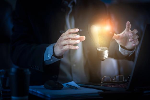 Geschäftsmann, der glühbirne der neuen ideen und der kreativität hält