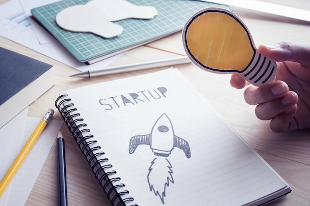 Geschäftsmann, der glühbirnenpapier mit dem zeichnen des starttextes auf notizbuch hält. kreativität, inspirationsideenkonzept.