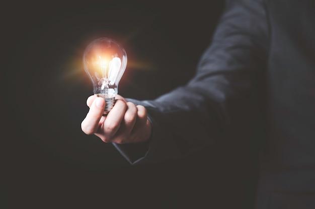 Geschäftsmann, der glühende glühbirne hält und computer-laptop verwendet, um geschäftsstrategieidee, kreative denkideen und innovationskonzept einzugeben.