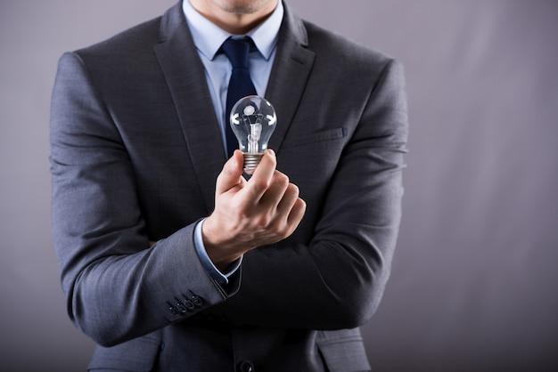 Geschäftsmann, der glühlampe anhält