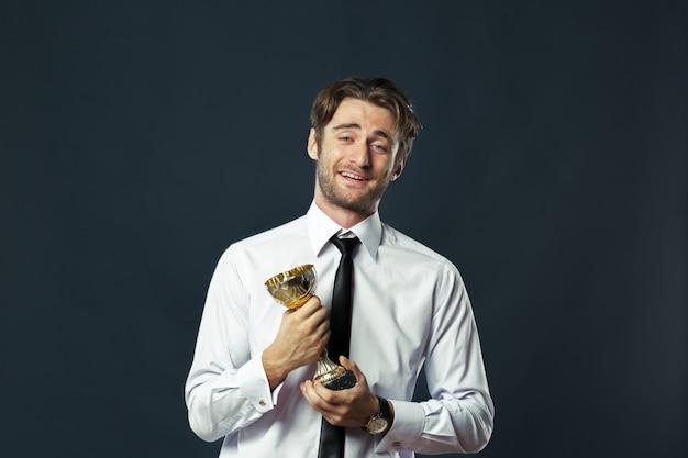 Geschäftsmann, der goldene cuptrophäe anhält