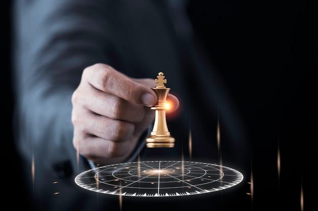 Geschäftsmann, der goldenes königschach hält und zum virtuellen zielpfeil wirft.