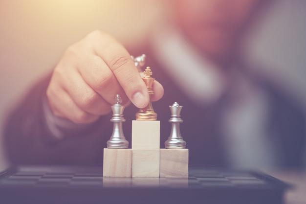 Geschäftsmann, der goldenes königschach zur siegerposition auf hölzernem würfel des schachspiels hält