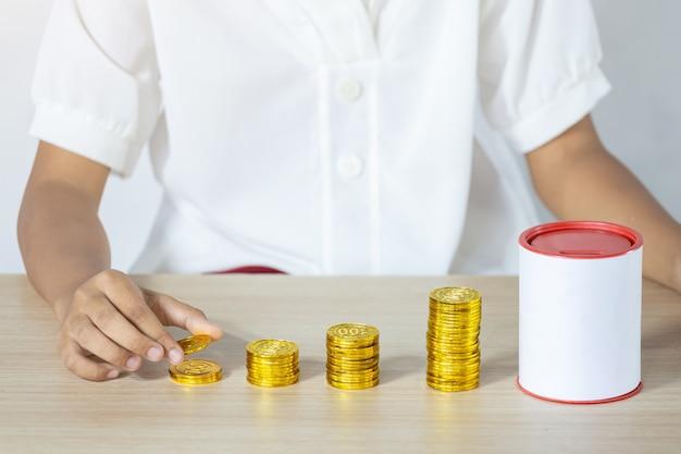Geschäftsmann, der goldmünzen hält, die in münzbank setzen.