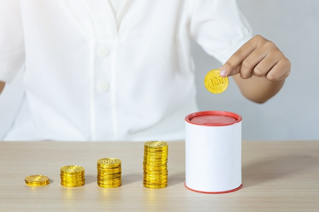 Geschäftsmann, der goldmünzen hält und in münzbank setzt