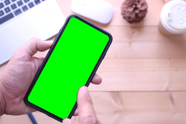 Geschäftsmann, der grünen schirm smartphone hält