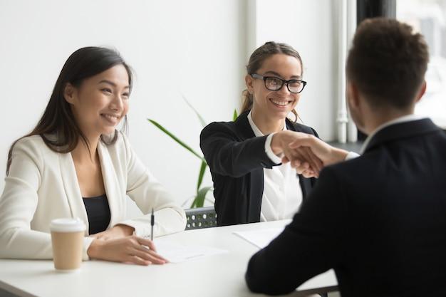 Geschäftsmann, der hand des weiblichen mitarbeiters während der firmasitzung rüttelt