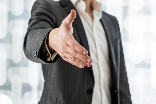 Geschäftsmann, der hand in handschlag anbietet