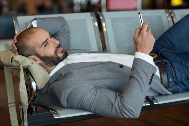 Geschäftsmann, der handy beim liegen auf stühlen im wartebereich verwendet