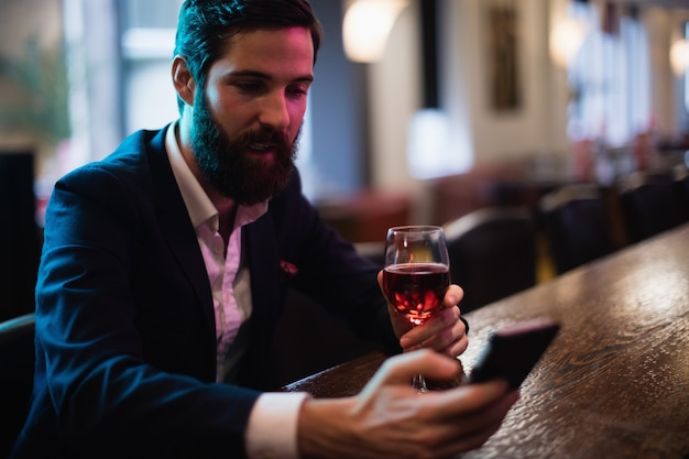 Geschäftsmann, der handy mit glas rotwein in der hand benutzt